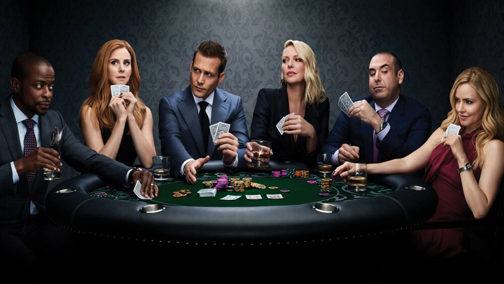 cast of suits sat around a table playing cards
