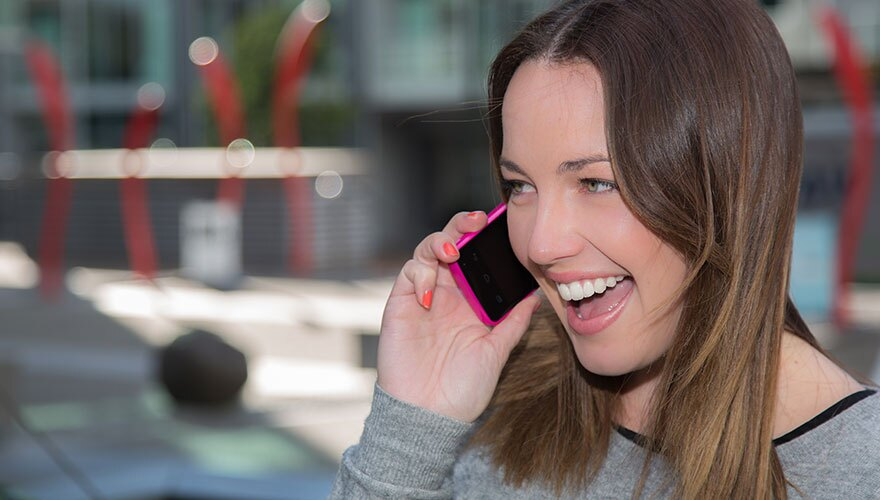 Smiling woman talking on a pink mobile phone.