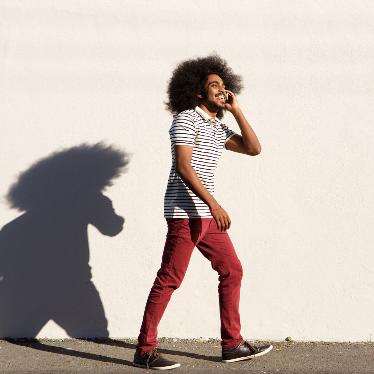 man walking and talking on mobile phone