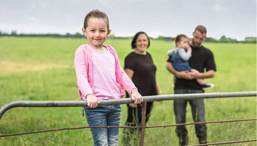 Young girl in pink top and jeans standing on a farm gate with family behind her smiling.