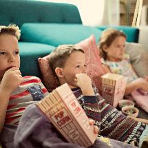 kids eating popcorn on floor watching a movie