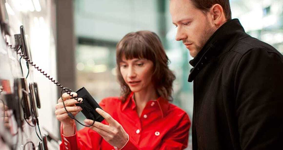 lady in red shirt showing a handset to a man in black coat